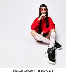 young brunette in short black shorts, a red sweatshirt, fashionable sneakers and white red polka dot socks asking for silence, a shh sign