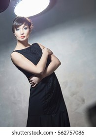 Young brunette shows beautiful expensive evening dresses.All photos were taken in Studio on the gray background of the ancient walls.In the frame there are elements of scenery and lighting equipment.