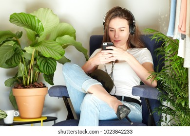 Young brunette sitting in armchair listening to music with earphones and smartphone.