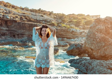 young brunette stand at a rocky shore in a boho-style dress, while the sun is setting