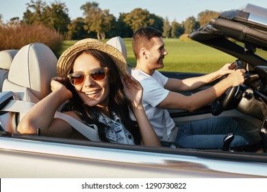 young brunette in summer hat riding cabriolet with boyfriend