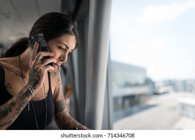 Young brunette tattooed woman portrait talking at the phone at the airport.