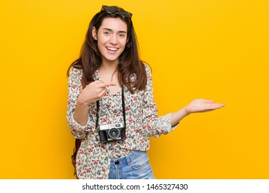 Young brunette traveler woman excited holding a copy space on palm.