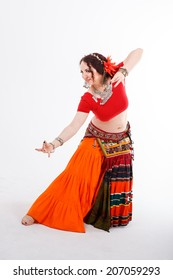 young brunette tribal dancer in national turkish costume dancing  with her hands on gray background in studio