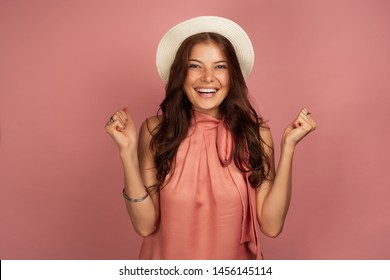 Young brunette wearing a hat smiles at the camera clenching her hands with delight