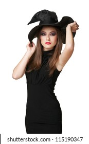 The  young brunette witch is standing in a black dress