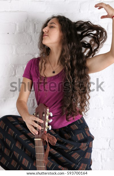 Young brunette woman with acoustic guitar in long skirt. Brick wall background.
