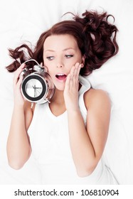 young brunette woman with alarm clock  in bed at home, top view