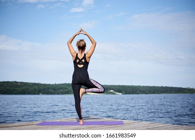 Young brunette woman with bare feet, wearing black and purple fitness outfit, stretching on violet yoga mat outside on wooden pier in summer. Fit girl, doing yoga poses by lake. Healthy lifestyle.
