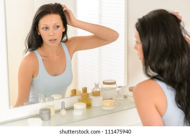 Young brunette woman in bathroom looking at herself in mirror