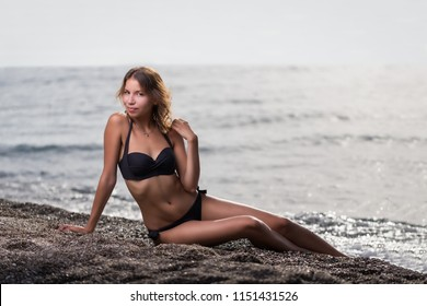 Young brunette woman with black bikini sitting on beach and posing
