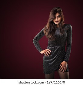 Young brunette woman in black dress posing on the cherrybackground