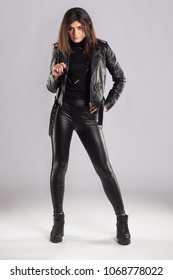 Young brunette woman in black leather jacket and pants posing on grey background