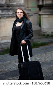 young brunette woman in black leather jacket standing in street with suitcase