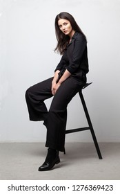 young brunette woman in black shirt and trousers sitting on chair on gray studio background
