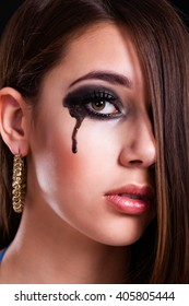 young brunette woman with a black tear on her cheek