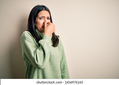Young brunette woman with blue eyes wearing turtleneck sweater over white background smelling something stinky and disgusting, intolerable smell, holding breath with fingers on nose. Bad smell