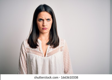Young brunette woman with blue eyes wearing casual t-shirt over isolated white background skeptic and nervous, frowning upset because of problem. Negative person.