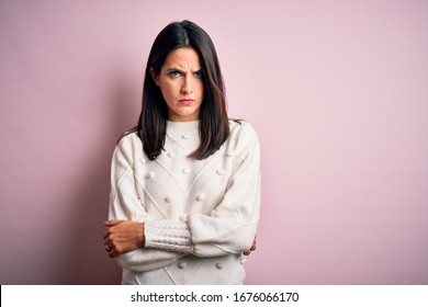 Young brunette woman with blue eyes wearing casual sweater over isolated pink background skeptic and nervous, disapproving expression on face with crossed arms. Negative person.