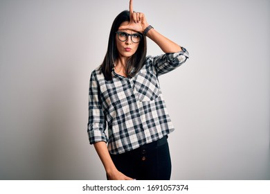 Young brunette woman with blue eyes wearing casual shirt and glasses over white background making fun of people with fingers on forehead doing loser gesture mocking and insulting.