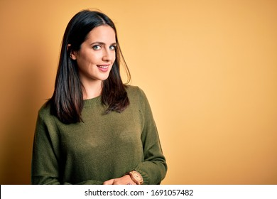 Young brunette woman with blue eyes wearing green casual sweater over yellow background with hands together and crossed fingers smiling relaxed and cheerful. Success and optimistic