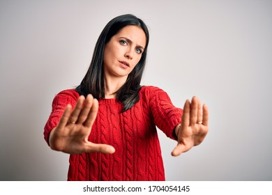 Young brunette woman with blue eyes wearing casual sweater over isolated white background doing stop gesture with hands palms, angry and frustration expression