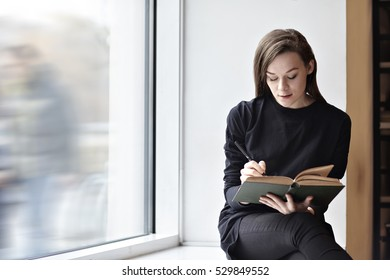Young brunette woman with a book in a public library. Sitting near window