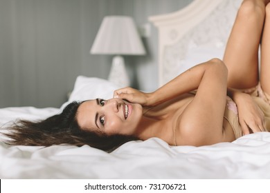 Young brunette woman in bride boudoir room laying on bad