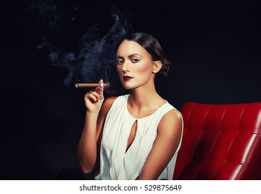 Young brunette woman in business style with cigar on red chair over smoky dark background. Studio portrait. Toned