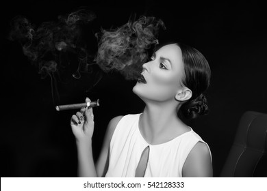 Young brunette woman in business style with cigar on red chair over smoky dark background. Studio portrait. Black and white