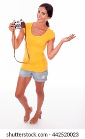 Young brunette woman with camera smiling while looking at camera and wearing a yellow t-shirt and short jeans on white background