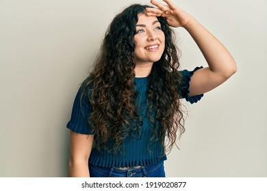Young brunette woman with curly hair wearing casual clothes very happy and smiling looking far away with hand over head. searching concept.
