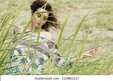 Young brunette woman dancing on nature in summer