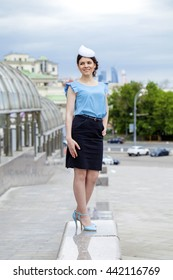 Young brunette woman in dark skirt and blue blouse, summer street outdoors