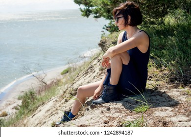 Young brunette woman in a dress sits on the edge of a cliff