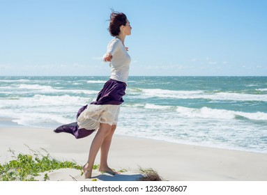Young brunette woman in dress stands on the hill by the sea