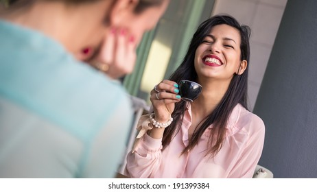 Young brunette woman drinking coffee with friend in a cafe outdoors. Shallow depth of field.