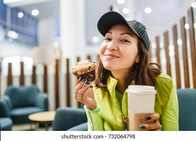 Young brunette woman drinking coffee and eating a delicious muffin cake in modern airport cafe, fastfood travel concept