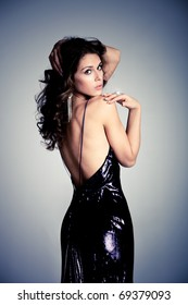 young brunette woman in elegant dress, studio shot