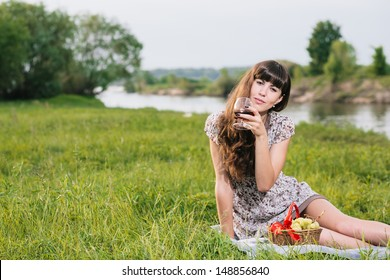 Young brunette woman enjoying picnic, lots of copy space