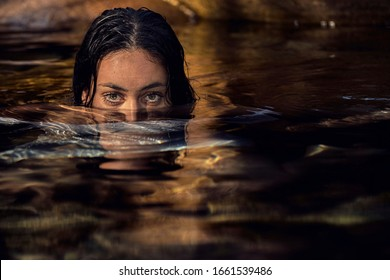 Young brunette woman with half of her face and her body submerged in the water looking straight ahead with her beautiful eyes