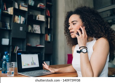 young brunette woman having business call and working in modern office with laptop – emancipation, concentration, dedication