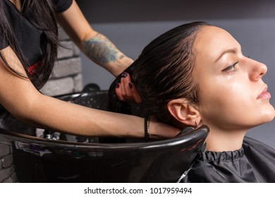 Young brunette woman having hair washed by hairdresser in washing sink in beauty salon