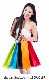 young brunette woman holding colorful shopping bags isolated on white background.