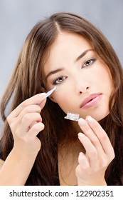 Young brunette woman holding contact lens in front of her eye