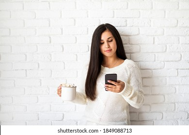 Young brunette woman holding a cup of marshmallow cocoa and using her mobile phone on white brick wall background
