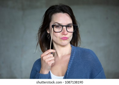 young brunette woman holding fake glasses to her face