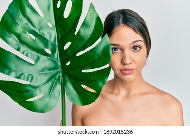 Young brunette woman holding green plant leaf close to beautiful face relaxed with serious expression on face. simple and natural looking at the camera.