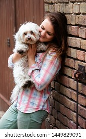 young brunette woman holding her little dog and standing at brick wall