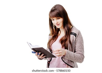young brunette woman holding a notebook and pen on white isolated background.
